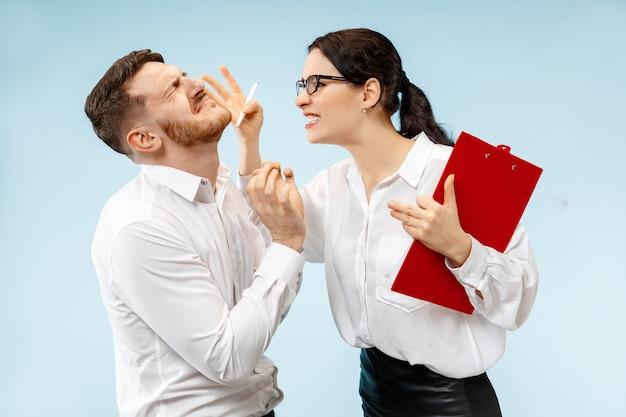 Zły szef. kobieta i jego sekretarz stojący w biurze lub w studio. bizneswoman krzyczy do swojego kolegi. modelki kaukaskie żeńskie i męskie. koncepcja relacji biurowych, ludzkie emocje