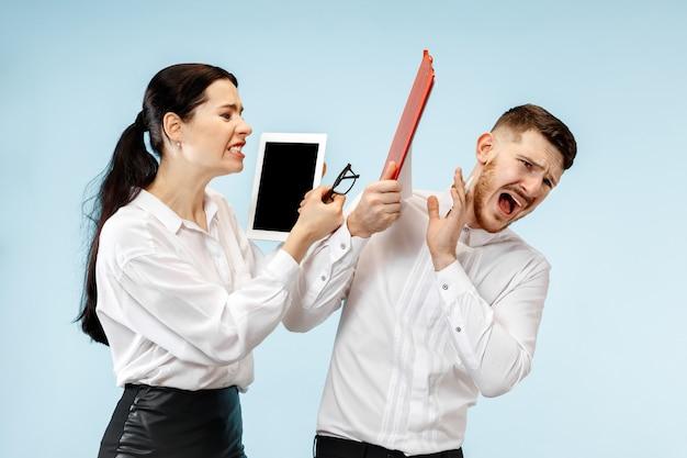 Zły szef. kobieta i jego sekretarz stojący w biurze lub w studio. bizneswoman krzyczy do swojego kolegi. modelki kaukaskie żeńskie i męskie.