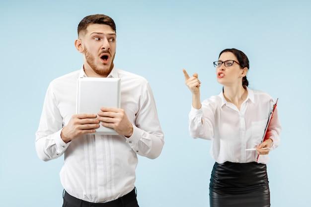 Zły szef. kobieta i jego sekretarz stojący w biurze lub w studio. bizneswoman krzyczy do swojego kolegi.