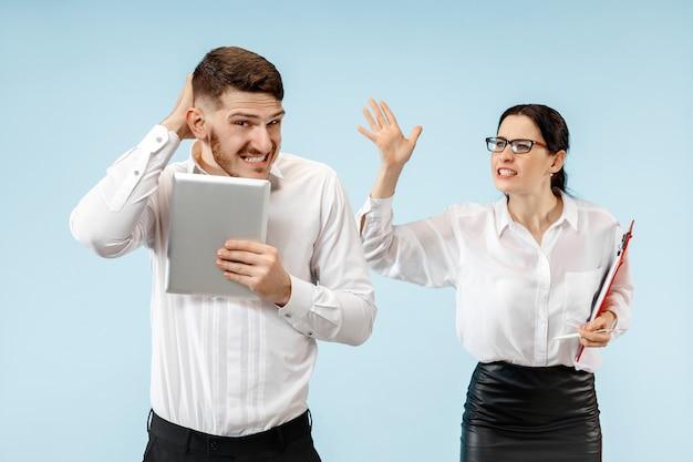 Zły szef. kobieta i jego sekretarz stojący w biurze lub w studio. businesswoman krzyczy do swojego kolegi. modelki kaukaskie żeńskie i męskie. koncepcja relacji biurowych, ludzkie emocje