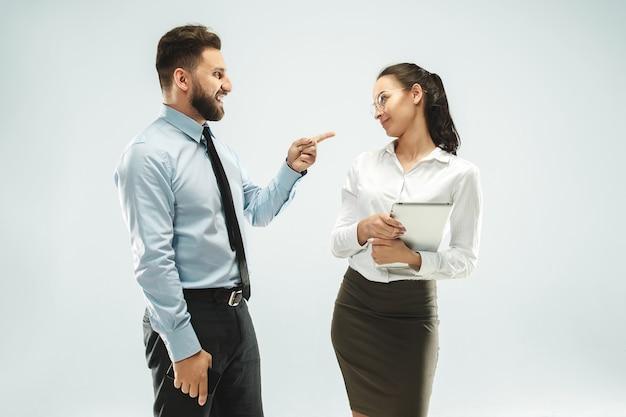 Zły szef. mężczyzna i jego sekretarz stojący w biurze lub studio.