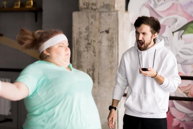Zły trener szkolenia otyłej kobiety