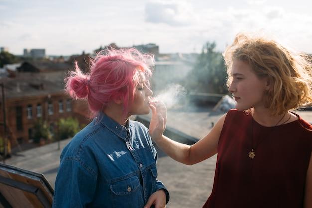 Zły wpływ. dziewczyna paląca papierosa z ręki koleżanki. ulica nastoletniego stylu życia. niebezpieczeństwa związane ze złymi skojarzeniami
