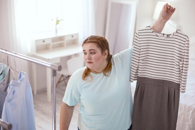 Zły wybór. rozczarowana młoda kobieta trzymająca pasiastą sukienkę, której nie lubi
