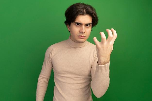 Zły wyglądający młody przystojny facet pokazujący gest tygrysa stylu na białym tle na zielonej ścianie