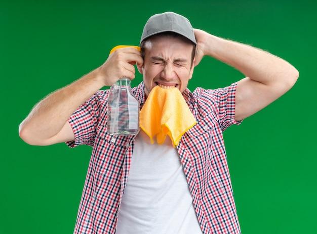 Zły z zamkniętymi oczami młody facet sprzątający w czapce trzymającej szmatkę do czyszczenia na ustach pokazujący samobójczy gest ze środkiem czyszczącym kładącym rękę na głowie odizolowany na zielonej ścianie