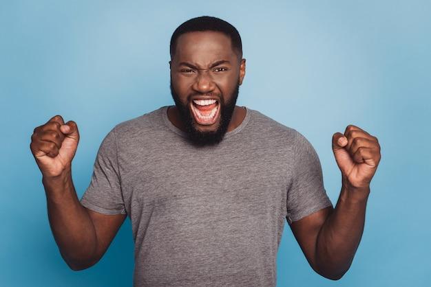 Zły zirytowany młody afrykański mężczyzna krzyczy, patrząc na kamerę odizolowaną na niebieskim tle koloru