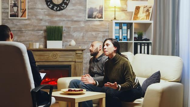 Zły żona na kanapie w terapii pary krzyczy. konflikt relacji.
