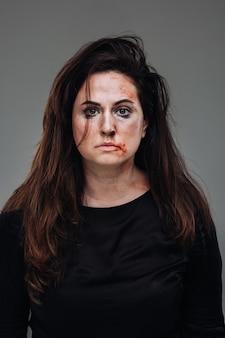 Zmaltretowana kobieta w czarnych ubraniach na odizolowanej szarej ścianie