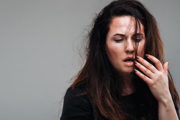 Zmaltretowana kobieta w czarnych ubraniach na odosobnionej szarej ścianie. przemoc wobec kobiet.
