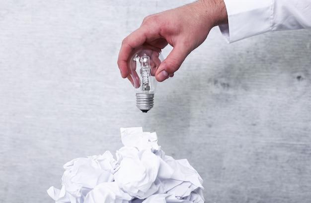 Zmarnowane papiery w koszu na śmieci z żarówką