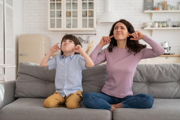 Zmarszczeni mama i syn siedzą na kanapie, zakrywając uszy głośną muzyką