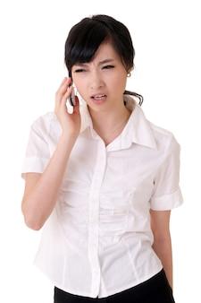 Zmartwiona biznesowa kobieta trzyma telefon komórkowy i słucha na białym tle.