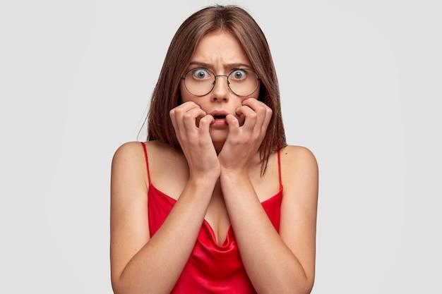 Zmartwiona brunetka młoda kobieta pozuje na białej ścianie