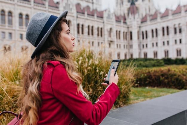 Zmartwiona ciemnowłosa kobieta w szarym kapeluszu korzystająca z gps podczas korzystania z atrakcji