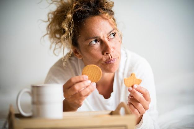 Zmartwiona dorosła kobieta herbatniki sith i kawa rano śniadanie w domu leżąc na łóżku - ładna kobieta w średnim wieku z myślami o jedzeniu i odżywianiu oraz problemami z wagą