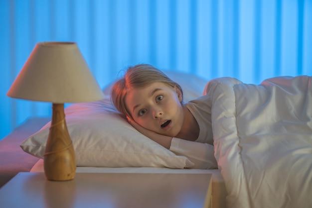 Zmartwiona dziewczyna leżała na łóżku. wieczorna pora nocna