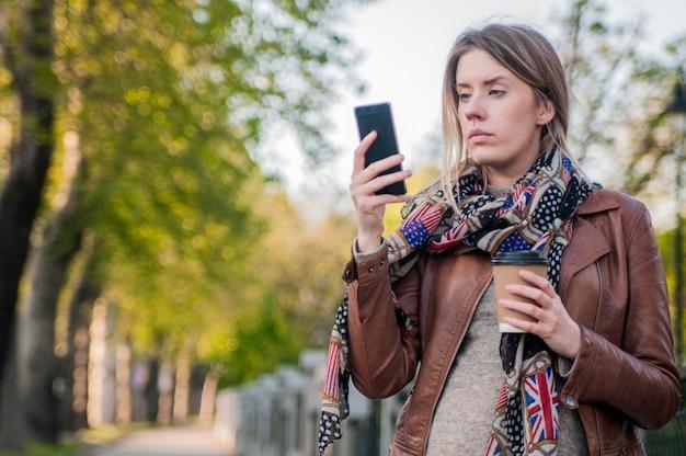 Zmartwiona dziewczyna nastolatek hipster patrząc na jej inteligentny telefon w parku z unfocused tle