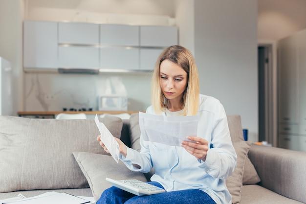 Zmartwiona gospodyni domowa płaci zawyżone rachunki siedząc na kanapie w domu, sfrustrowana pracą i miesięcznym dochodem