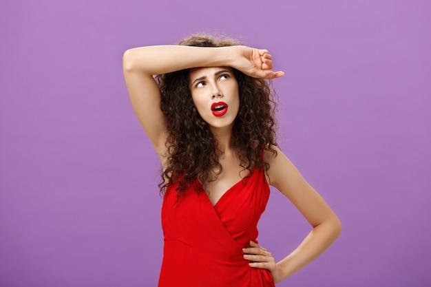 Zmartwiona i zmęczona atrakcyjna europejska kobieta z kręconymi fryzurami w czerwonej sukni wieczorowej ocierająca pot z czoła patrząca w prawy górny róg zakłopotana i wyczerpana na fioletowym tle.