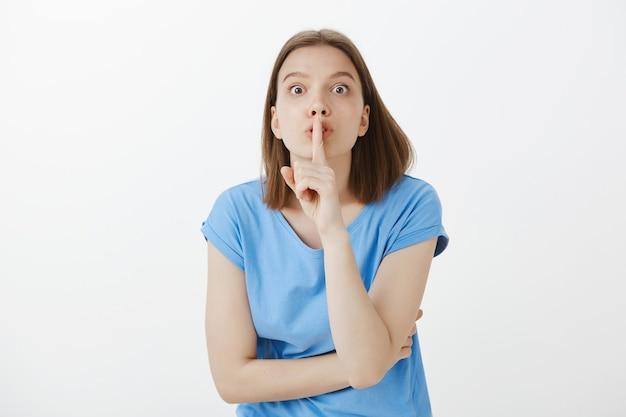 Zmartwiona kobieta uciszająca się z szalonymi oczami, powiedz, żebyś był cicho