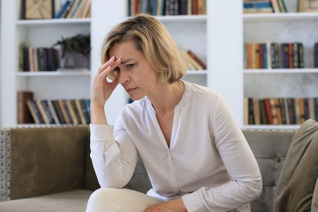 Zmartwiona kobieta w średnim wieku siedzi na kanapie w salonie.