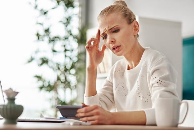 Zmartwiona kobieta z kalkulatorem w domowym biurze