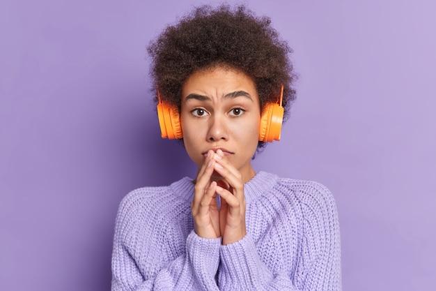 Zmartwiona kobieta z kręconymi włosami trzyma ręce blisko ust i uczy się obcych słów z audio, nosi słuchawki stereo, nosi swobodny sweter