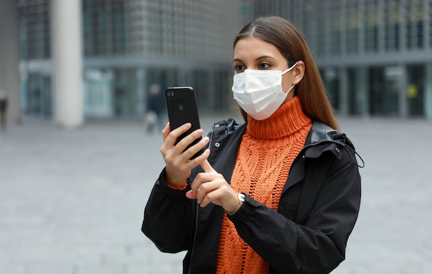 Zmartwiona kobieta z maską ochronną czytająca informacje na swoim smartfonie na ulicy nowoczesnego miasta