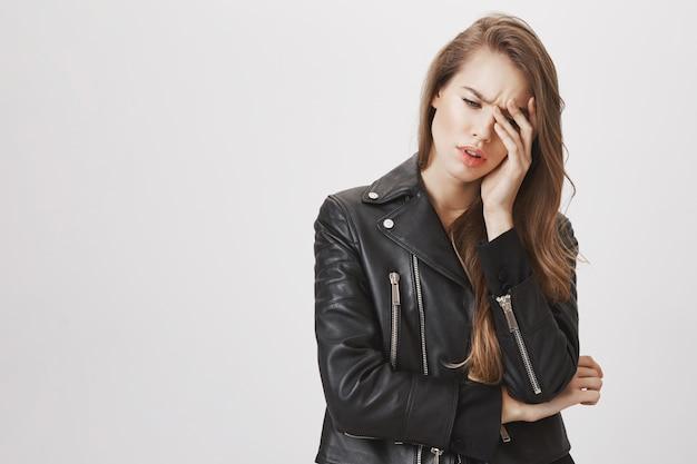 Zmartwiona lub zmęczona kobieta patrzy na twarz z westchnieniem