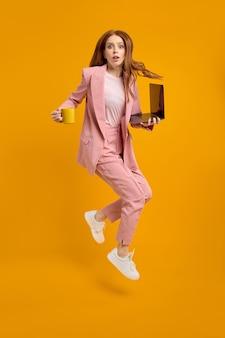 Zmartwiona miła, wesoła, odnosząca sukcesy kobieta, liderka skacząca w powietrzu, niosąca laptopa i filiżankę kawy w biegu...