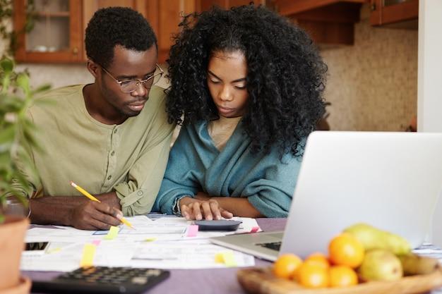 Zmartwiona młoda afrykańska rodzina składająca się z dwojga, mająca problemy finansowe. nieszczęśliwa kobieta z fryzurą afro za pomocą kalkulatora podczas robienia papierkowej roboty z mężem, który wypełnia kartki ołówkiem