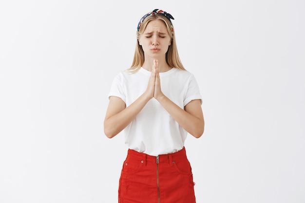 Zmartwiona młoda blond dziewczyna pozuje pod białą ścianą