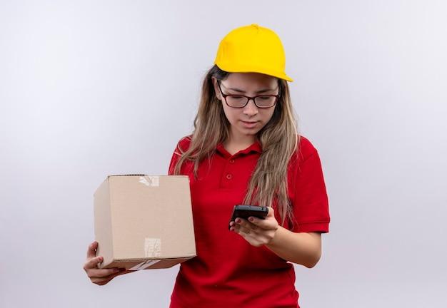 Zmartwiona młoda dostawa dziewczyna w czerwonej koszulce polo i żółtej czapce trzymając pudełko, patrząc na ekran swojego smartfona