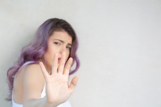 Zmartwiona młoda dziewczyna pokazuje gest stop na szarej ścianie. miejsce na tekst