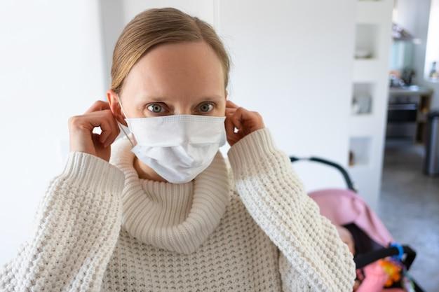 Zmartwiona młoda kobieta jest ubranym medyczną twarzy maskę