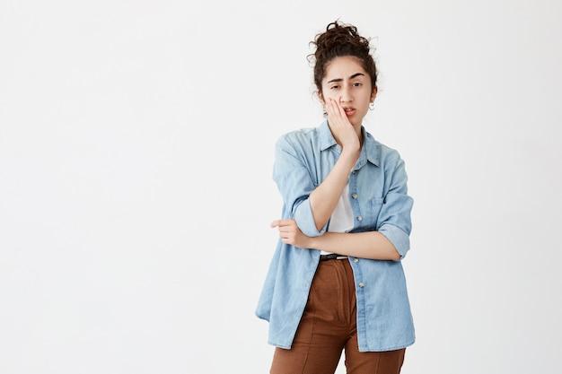Zmartwiona młoda kobieta o ciemnych włosach w kok w dżinsowej koszuli dotyka jej policzka i patrzy w bok z wątpliwym i sceptycznym wyrazem twarzy, podejmuje ważną decyzję życiową, marszczy brwi