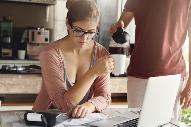 Zmartwiona młoda kobieta obliczająca wydatki rodzinne i sporządzająca domowy budżet za pomocą zwykłego laptopa i kalkulatora w kuchni, podczas gdy jej mąż stoi obok niej i nalewa gorącą kawę do jej kubka