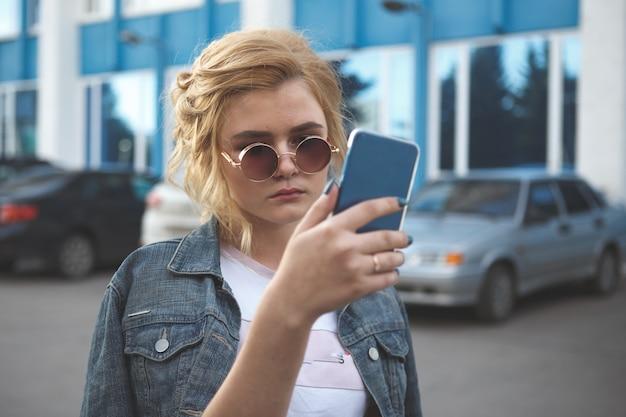 Zmartwiona nastolatka patrząca na swój smartfon w parku z nieostrym tłem