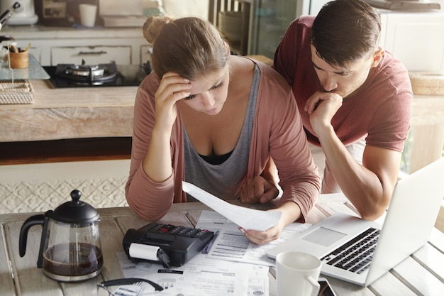 Zmartwiona para przeglądająca finanse rodziny i obliczająca wydatki