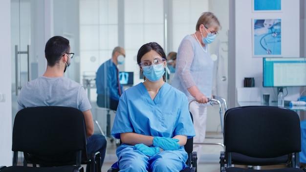 Zmartwiona pielęgniarka z maską na twarz przed koronawirusem, siedząc na krzesłach w szpitalnej poczekalni. niepełnosprawna starsza kobieta z chodzeniem w korytarzu szpitala.