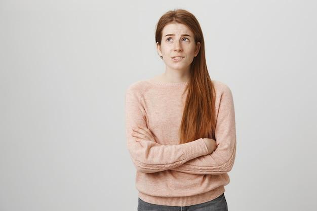 Zmartwiona ruda nastolatka wygląda na zaniepokojoną, ma problemy