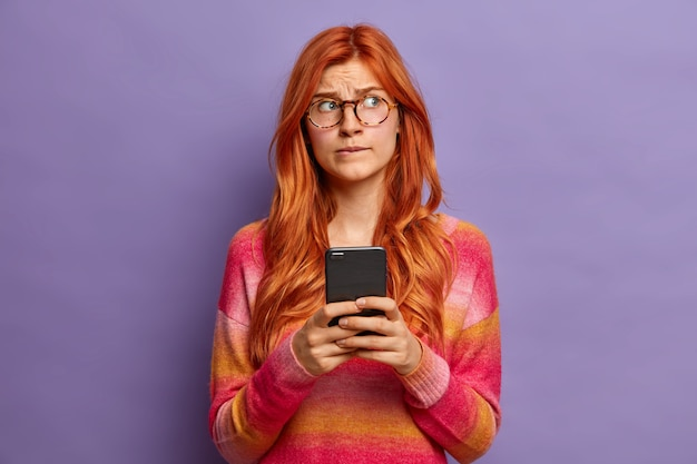 Zmartwiona rudowłosa europejka zastanawia się, jakiej odpowiedzi udzielić w związku z ostatnio otrzymaną wiadomością, nosi okulary optyczne i sweter z wyrazistym wyrazem twarzy.