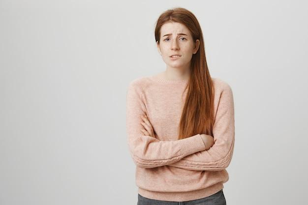 Zmartwiona rudowłosa nastolatka wyglądająca na zmartwioną, ma problemy