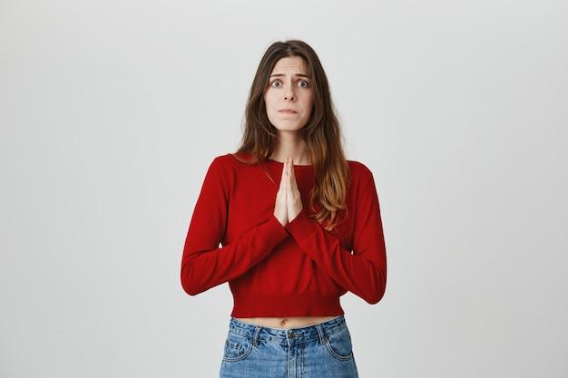 Zmartwiona śliczna dziewczyna błaga o pomoc, prosząc o radę rękami w geście modlitwy