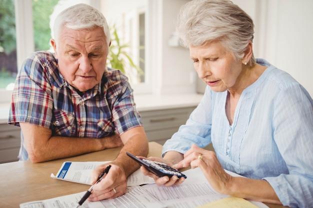 Zmartwiona starsza para sprawdza ich rachunki w domu