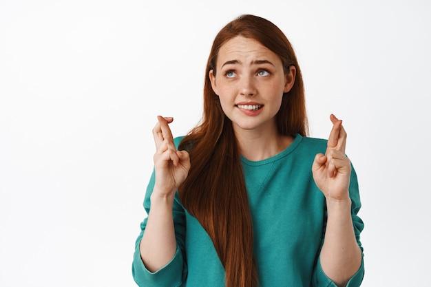 Zmartwiona studentka z rudymi włosami, skrzyżowanymi palcami i życząca, oczekująca dobrych wieści, patrząca w górę z nerwową, pełną nadziei twarzą, stojąca na białym