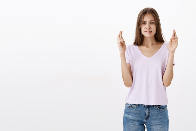 Zmartwiona urocza brunetka, która ma nadzieję, że zdała egzaminy na uniwersytet, marzy o przygryzaniu dolnej wargi i marszczeniu brwi, patrząc intensywnie trzymających palce na szczęście, gdy marzy