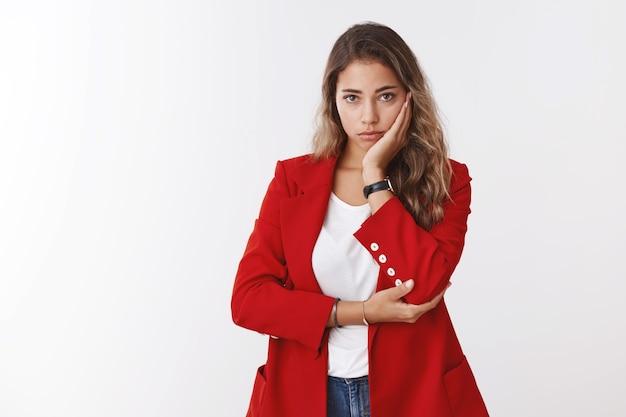 Zmartwiona, zakłopotana, zmartwiona, urocza smutna kobieta z 25-lecia w czerwonej kurtce, trzymająca twarz w dłoni, pochylona głowa, wyglądająca ponuro, zdenerwowana awaria aparatu, nie może rozwiązać sytuacji, stojąca biała ściana