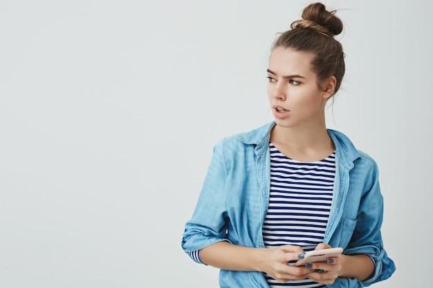 Zmartwiona zaniepokojona młoda kaukaska kobieta ubrana w hairbun, luźną koszulę, wyglądająca na bok zakłopotana zmartwiona marszczy brwi otrzymująca niepokojącą nieprzyjemną wiadomość reagująca kłopotliwą wiadomością, trzymająca smartfon